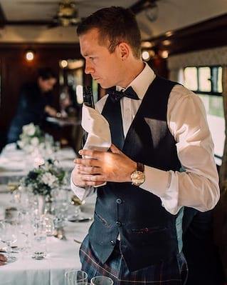 Steward in a waistcoat and bow tie polishing glasses