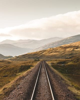 Train tracks leading into a dramatic mountainous landscape in Scotland