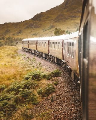 A row of train carriages curving along a train track in Scotland