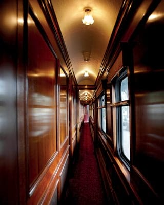 French-polished, wood-panelled, lamplit train corridor with a burgundy carpet