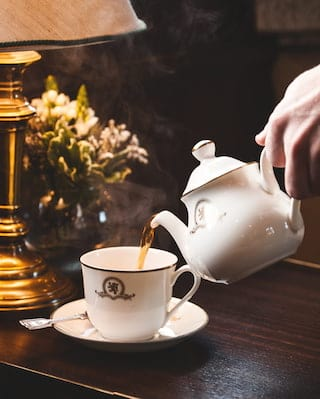 Close-up of tea being poured into a china teacup from a matching teapot