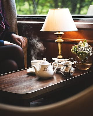 Steaming cup of tea on a mahogany coffee table under a lit table lamp