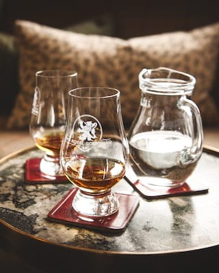 Whisky in two Glencairn glasses engraved with the Royal Scotsman logo