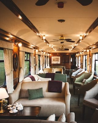 Lamplit train observation car with plush tweed and tartan sofas and armchairs