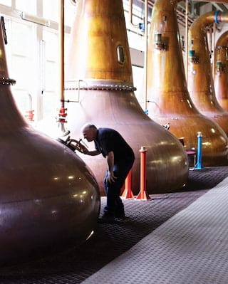 Close-up of giant copper stills in a row in a glass-walled whisky distillery