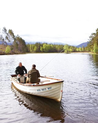 Fishermen in a rowing boat on a loch surrounded by tall pine trees
