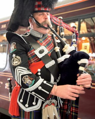 Bagpiper in a kilt and full regalia performing next to burgundy train carriages