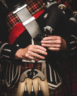 Close-up of a kilted piper's hands playing a bagpipe