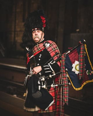Bagpiper in full regalia with a red tartan sash holding a set of bagpipes