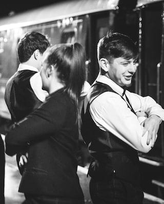 Black and white image of guests and stewards ceilidh dancing on a train platform