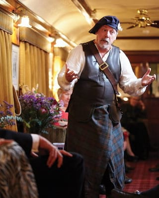 Storyteller in traditional highland dress performing a Scottish folk tale