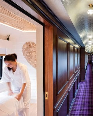 View from a wood-panelled train corridor of a light and airy spa treatment room