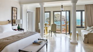Light and airy hotel suite with vast pillowy bed and polished tile floors