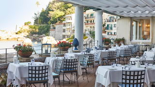 Open-air restaurant terrace with rows of linen-coated tables overlooking Taormina