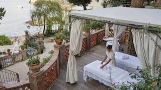 Spa therapist preparing an outdoor massage table under a garden gazebo