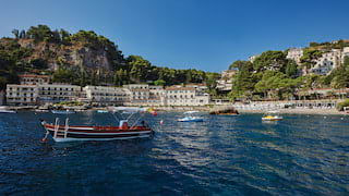 Boats bobbing in Taormina bay with grand residences lining the shore