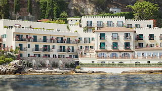 Grand hotel with clay tiled roof and cream coloured arches on the shoreline