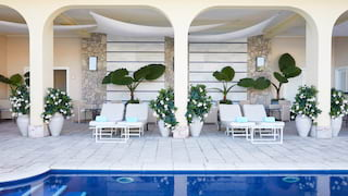 Mirror-still hotel pool next to a stone-tiled patio dotted with sunbeds and palms