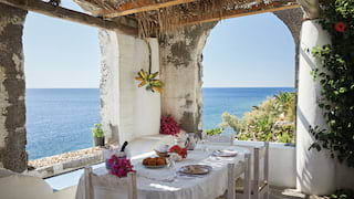 Formal dining table on a rustic open-air terrace with vines and sea views