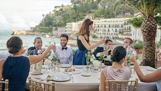 Guests at a formal wedding table on an outdoor terrace overlooking Taormina
