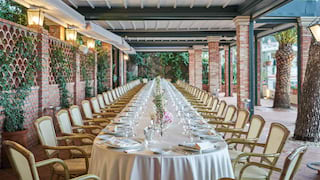 Long banquet table set for a wedding under a lamplit pergola surrounded by vines