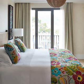 King-size bed in a light and airy hotel room with vibrant patterned bedspread