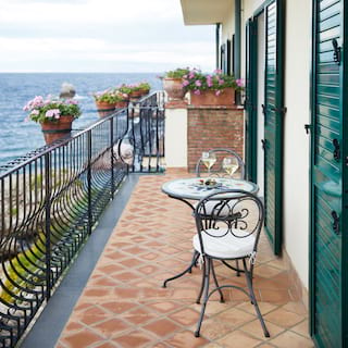 Balcony with black iron railings, clay tiles, breakfast table and sea views