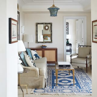 Hotel suite lounge area with a blue patterned rug and beige soft furnishings