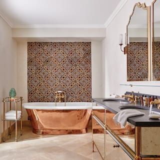 Vast suite bathroom with gleaming copper standalone tub and patterned wall tiles