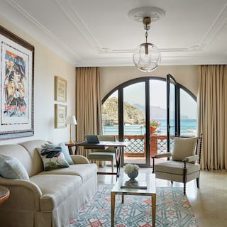 Spacious hotel suite living room with large arch window overlooking the sea