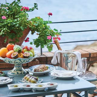 Close-up of a balcony breakfast table laden with champagne and breakfast dishes