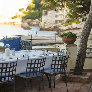 Restaurant terrace with a linen-coated table and elegant wrought-iron chairs