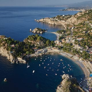 Aerial view of yachts bobbing in Taormina bay with residences coating the hills