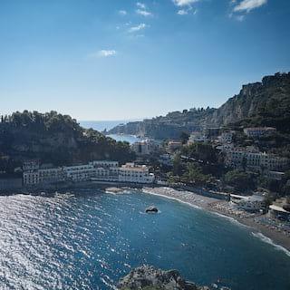 Belmond Villa Sant'Andrea on the shore of Taormina bay under blue skies