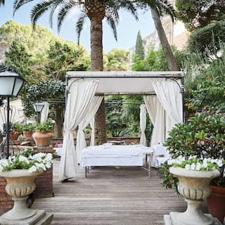 Gazebo with tied linen drapes over a massage table on a garden terrace