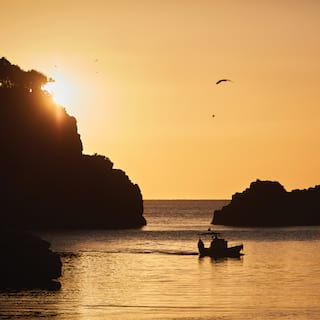 Silhouette of a sailing boat sailing in a rocky bay in an orange sunset