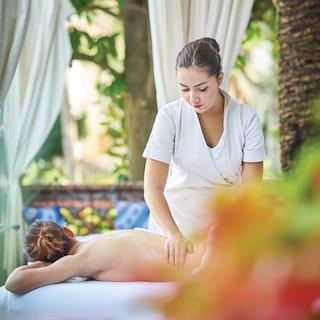 Spa therapist massaging a guest in an open air spa gazebo