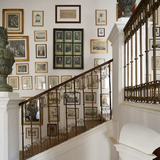 Large feature wall dotted with portrait picture frames above a marble stair