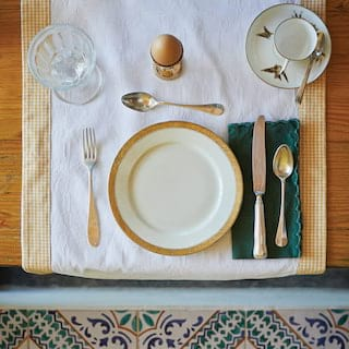 Birds-eye-view of a table setting with a gold-rimmed base plate and a boiled egg