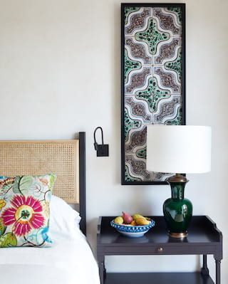 Vibrant floral pillow on a bed next to a side table with fruit and a green lamp