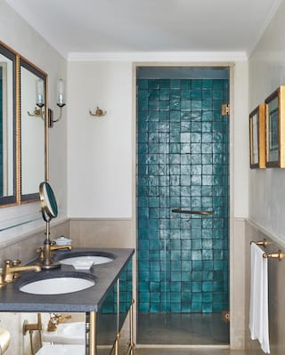 Hotel bathroom with teal shower tiles and gold and beige accents