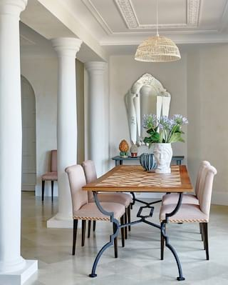 Hotel suite dining table with dusky pink chairs and contemporary decorative vases