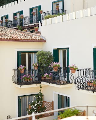 Balconies with ornate iron railings and pink potted flowers on a hotel exterior