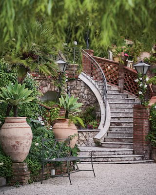 Stone steps curving from a patio with Grecian-style plant pots and lush foliage