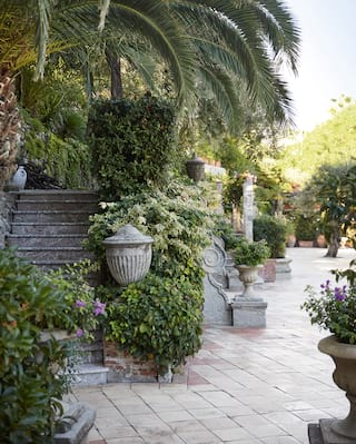 Italian garden with Grecian flower pots brimming with purple flowers and foliage