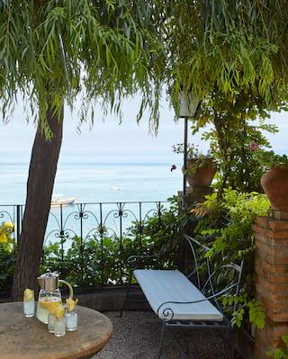 Iron-work garden bench in a garden balcony overlooking Taormina bay