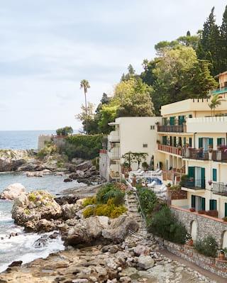 A grand hotel unfolding along a rocky shoreline in Taormina bay