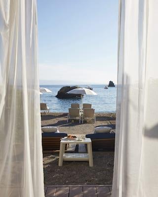 View through linen drapes of sunbeds under a white parasol on a shoreline