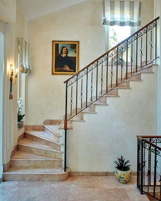 Renaissance portrait hanging beside clay tiled stairs with wrought-iron railings
