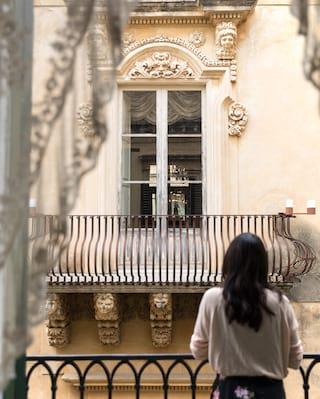 Lady at a Juliet balcony gazing across to a Juliet balcony opposite